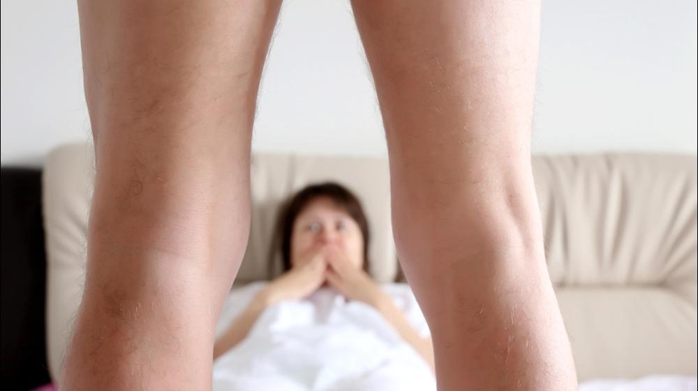 אשה במיטה מביטה בזקפה של גבר. ShutterStock