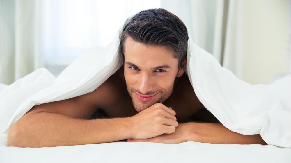 גבר מרוצה במיטה. ShutterStock