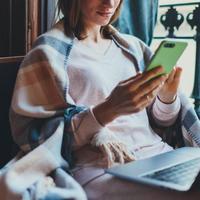 אישה עם סמארטפון ומחשב נייד. ShutterStock