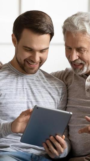 אב ובנו גולשים באינטרנט באמצעות טאבלט. ShutterStock