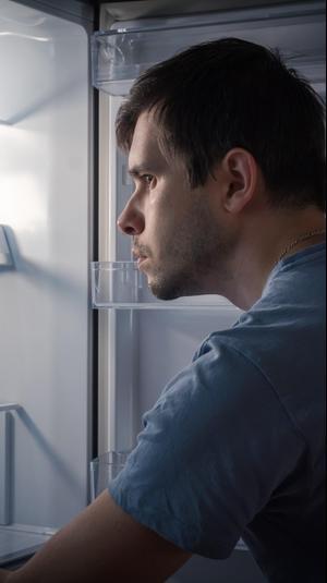 גבר מביט במקרר ריק. ShutterStock