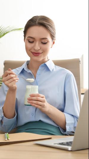אישה במשרד אוכלת יוגורט. ShutterStock
