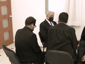 יושב בקצה האולם מוקף בעורכי דינו: נתניהו התייצב לפתח שלב העדויות במשפטו  5.4.21. פול קונטקט, אתר רשמי