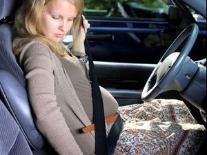 אישה בהריון שמה חגורת בטיחות ברכב. By ambrozinio, ShutterStock