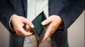 איש עסקים מחזיק ארנק ריק. ShutterStock