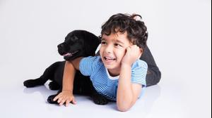 ילד מתכרבל עם כלב. ShutterStock