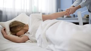 אמא מנסה להעיר ילדה ישנה בבוקר. ShutterStock