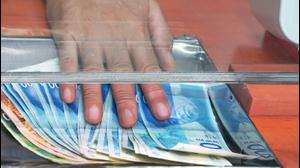 הפקדת כסף מזומן בבנק. ShutterStock