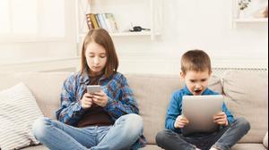 ילד וילדה גולשים בסמארטפון ובטאבלט. ShutterStock