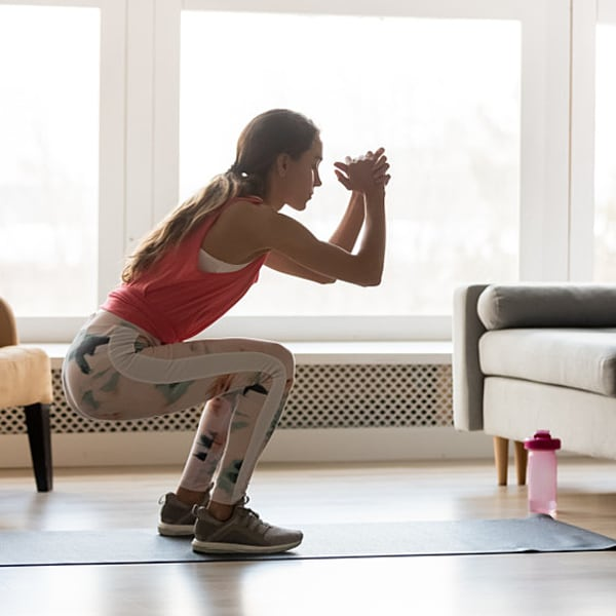 אישה עושה סקוואט באימון ביתי. ShutterStock