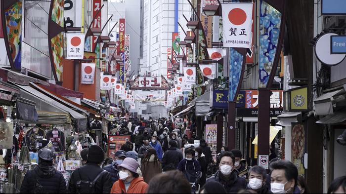 תושבים עם מסיכות מתהלכים ברחוב קניות מרכזי בטוקיו לאחר הטלת מגבלות להתמודדות עם התפרצות נוספת של קורונה במדינה. AP