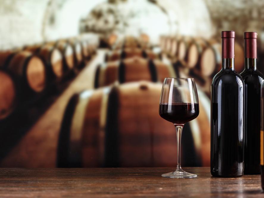 יין אדום על רקע חביות של יקב. ShutterStock