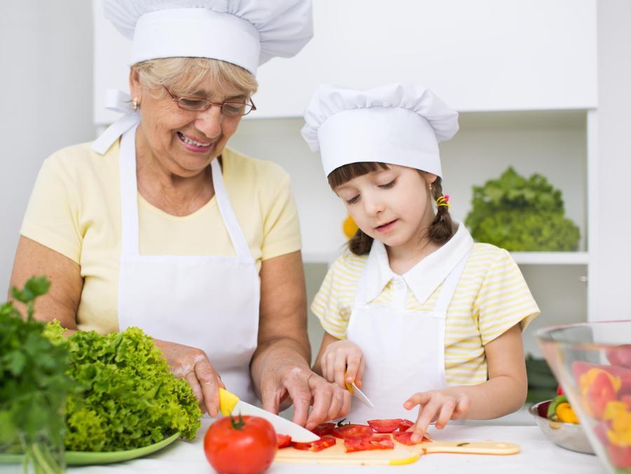 סבתא מבשלת עם נכדה. ShutterStock