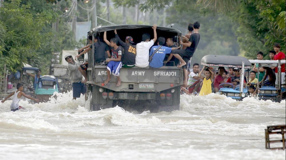 אנשים נמלטים משיטפונות בצפון הפיליפינים בעקבות סופת טייפון, 20 באוקטובר 2015