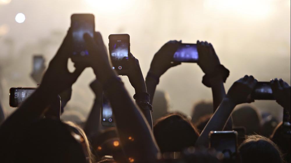 אוהדים בקהל מצלמים בפלאפונים טקס חלוקת פרסים בטורנטו, קנדה
