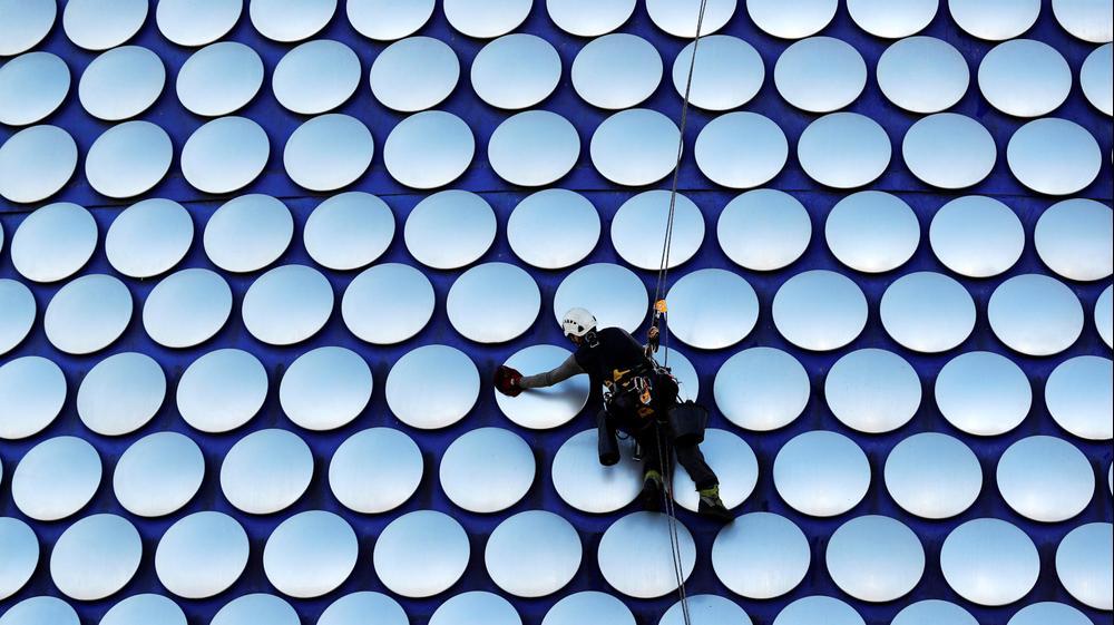 עובד מנקה את בניין סלפרידג'ס בבירמינגהם, בריטניה