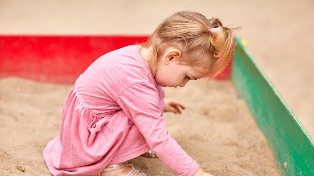 ילדה משחקת בארגז חול. ShutterStock