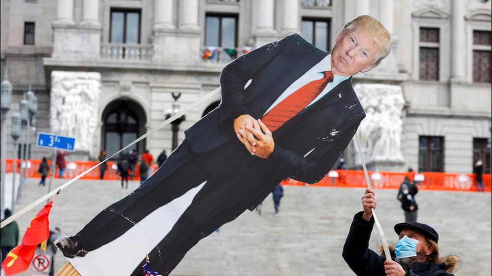 מפגין נגד טראמפ מסיר בובת קרטון בדמותו של הנשיא היוצא לקראת מחאה צפויה של תומכיו עם השבעתו של הנשיא הנבחר ביידן, פנסילבניה. רויטרס