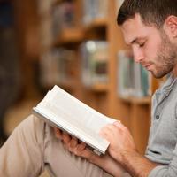 בחור צעיר יושב וקורא ספר. ShutterStock