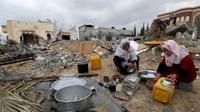 נשים פלסטיניות שוטפות כלים ליד בית הרוס בצפון רצועת עזה ב-13 בינואר 2020