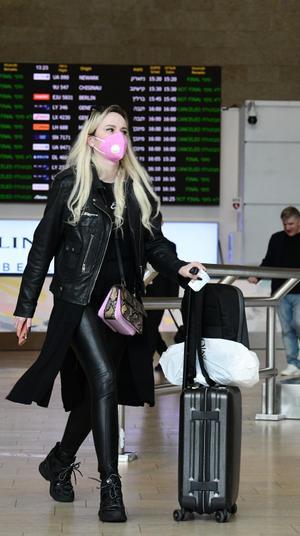 נוסעת מתגוננת עם מסכה מנגיף הקורונה בשדה התעופה בן גוריון 10 במרץ 2020