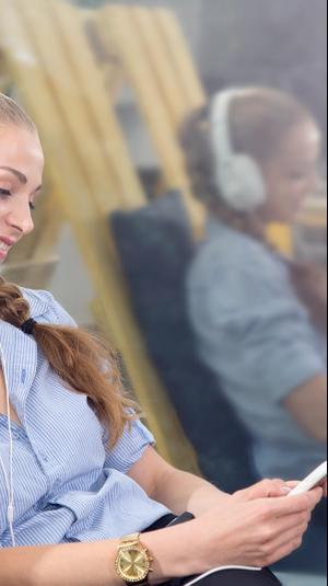 בחורה צעירה מקשיבה ספר דיגיטלי. ShutterStock