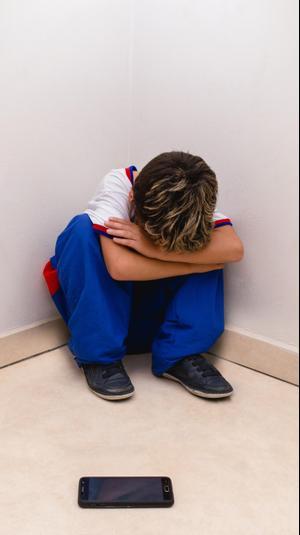 ילד עצוב בפינה סובל מבריונות ברשת. ShutterStock