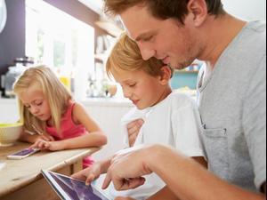 הורים וילדים מביטים במסכים בזמן ארוחה משפחתית