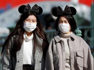 אנשים מתגוננים עם מסכה מנגיף הקורונה בדיסנילנד, טוקיו, יפן 28 בפברואר 2020