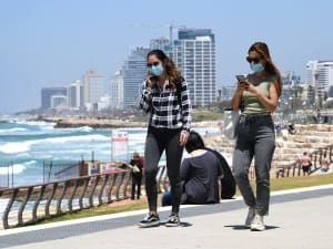 עוטים מסכה לצורך התגוננות מנגיף הקורונה סמוך לחופי תל אביב 7 במאי 2020