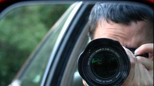 אדם יושב במכונית ומצלם. ShutterStock