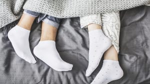 זוג עם גרביים במיטה. ShutterStock