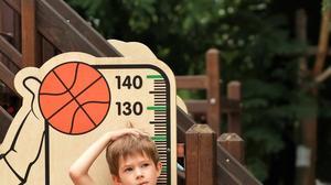 ילד מודד את הגובה שלו בגינת משחקים