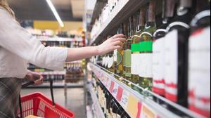 אישה קונה אלכוהול בסופרמקרט. ShutterStock