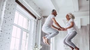 גבר ואישה מבוגרים קופצים בשמחה על מיטה
