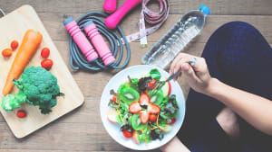 בחורה אוכלת סלט מוקפת באביזרי כושר, בקבוק מים וסרט מדידה
