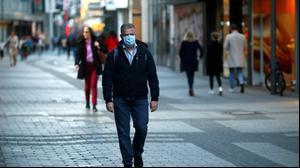אדם הולך כשהוא עוטה מסיכה נגד הקורונה בקלן, גרמניה, 18 במרץ 2020