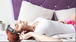 אשה עם אוזניות במיטה