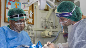 רופאי שיניים לבושים בציוד מגן מפני נגיף הקורונה מטפלים במטופל במרפאת שיניים