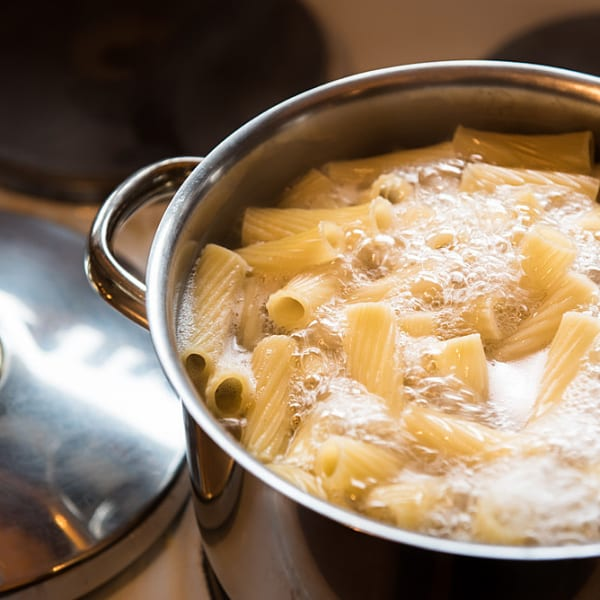 בישול פסטה בסיר מים רותחים. ShutterStock