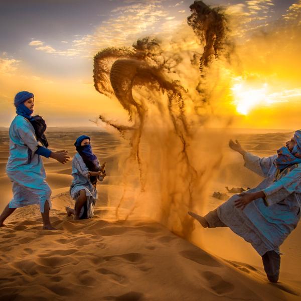 מדריכי שיירת גמלים בני טוראג משתעשעים בחולות מרזוגה שבמדבר סהרה, מרוקו