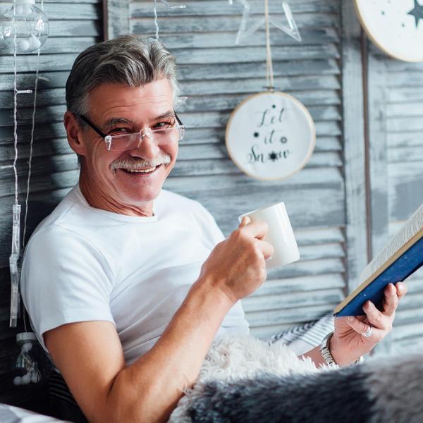איש מבוגר עם כוס תה קורא ספר. ShutterStock