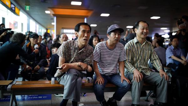 אזרחים בקוריאה הדרומית צופים בפגישתם של נשיא ארצות הברית דונלד טראמפ ושליט קוריאה הצפונית קים ג'ונג און בסינגפור, 12 ביוני 2018