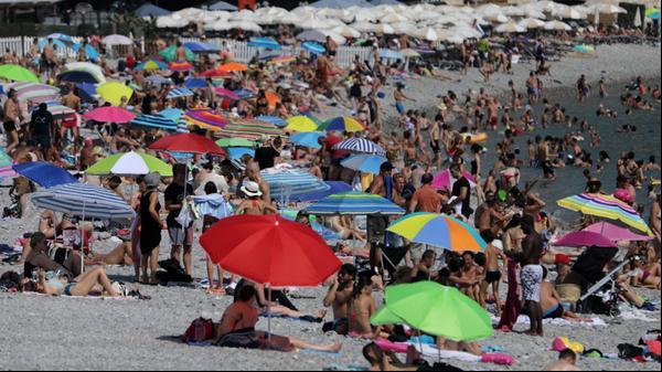 שמשיות מקשטות חוף הומה אנשים בזמן גל חום בניס, צרפת