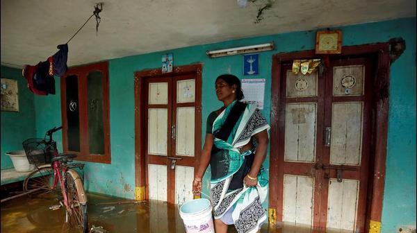 אישה מרחיקה מים מפתח ביתה, לאחר גשמים עזים שפקדו את צ'נאי, הודו.