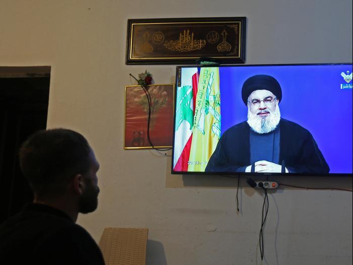 """אדם צופה בנאום של מזכ""""ל חיזבאללה חסן נסראללה בחנות בחולה, דרום לבנון, 29 בספטמבר"""