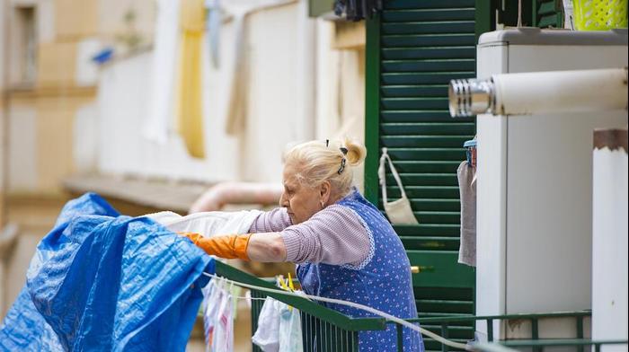 אישה מבוגרת תולה כביסה על חבל במרפסת בית בנאפולי, איטליה. ShutterStock