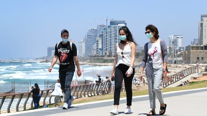 עוטים מסכה לצורך התגוננות מנגיף הקורונה סמוך לחופי תל אביב (צילום: ראובן קסטרו)