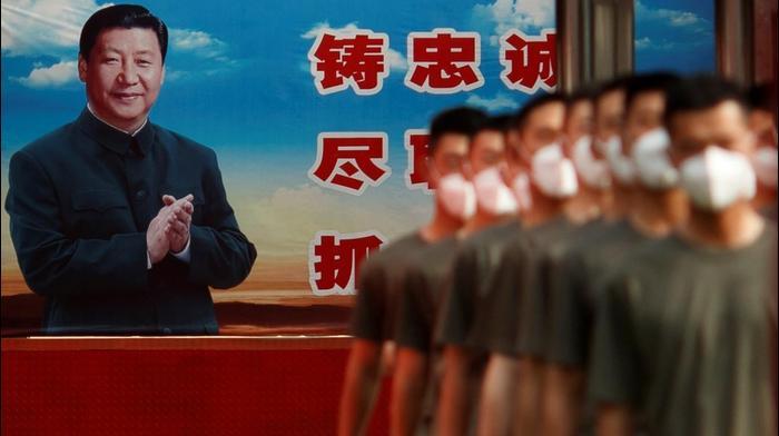 שוטרים מחוץ למבנה הפרלמנט של סין, בייג'ינג, מאחורי כרזה של הנשיא שי ג'ינפינג, 22 במאי 2020
