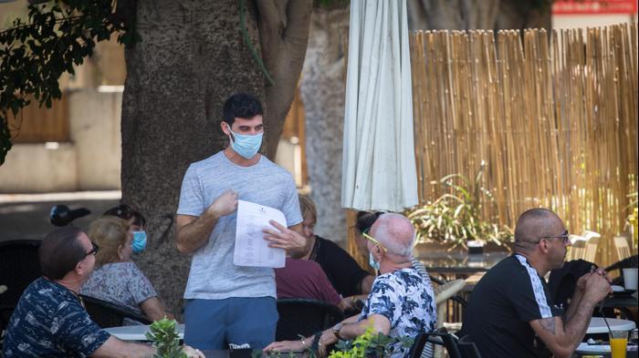 לקוחות במסעדה עוטים מסיכות להתמגנות מפני נגיף הקורונה, תל אביב. 15 ביולי 2020. מרים אלסטר, פלאש 90, פלאש 90